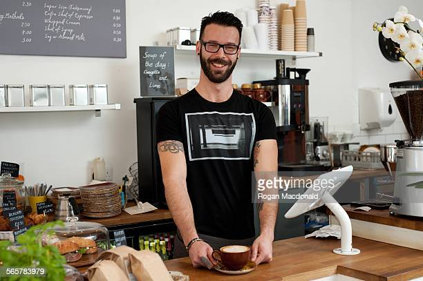 Portrait of cafe waiter serving coffee from counter