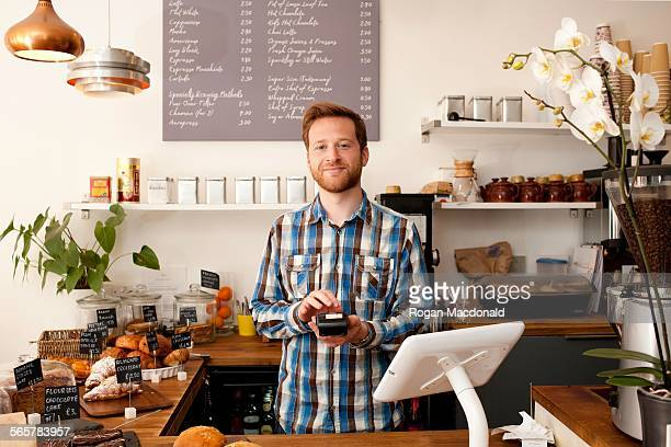 Portrait of cafe waiter with card machine behind counter