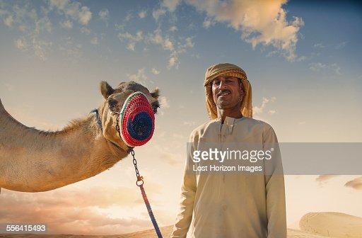 Portrait of camel and bedouin in desert, Dubai, United Arab Emirates