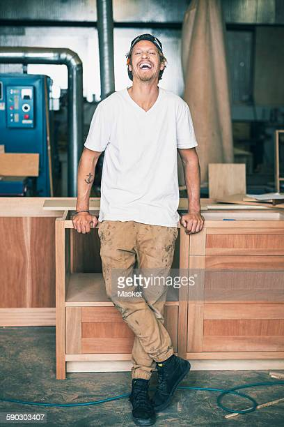 Portrait of carpenter laughing while standing at workshop