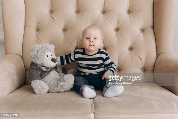 Portrait of Caucasian baby boy sitting on love seat with teddy bear