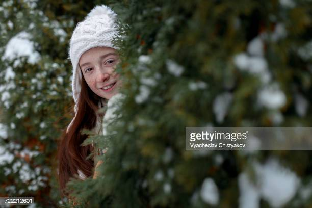 Portrait of Caucasian girl hiding behind tree in winter
