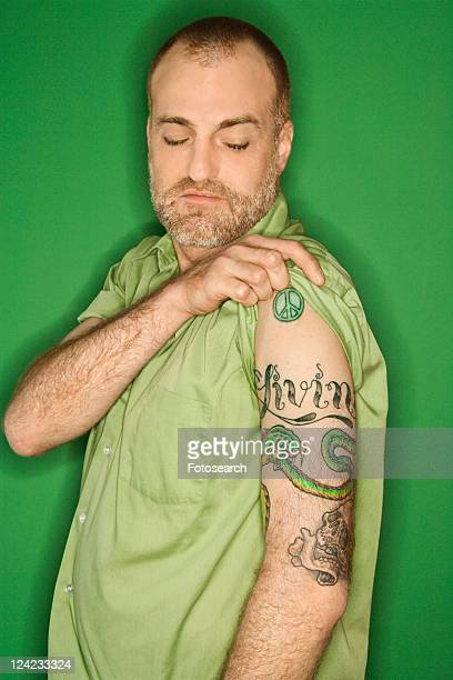 Portrait of Caucasian man pulling up sleeve to show tattoo standing against green background.
