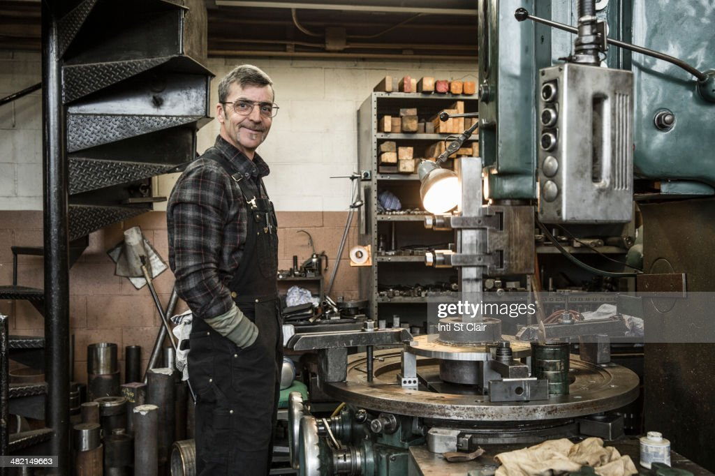 Portrait of Caucasian man smiling in metal shop