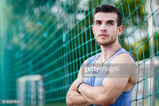 Portrait of caucasian muscular man leaning on sports football nets : Stock Photo
