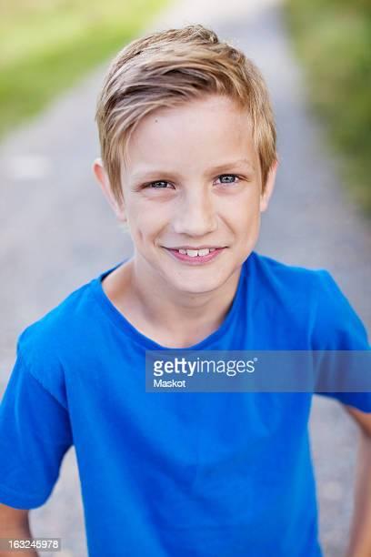 Portrait of Caucasian pre-adolescent boy standing on road smiling