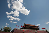 A portrait of Chairman Mao and red flags fluttering on the Rostrum in Tiananmen Square Beijing China Tiananmen Square is a large city square in the...