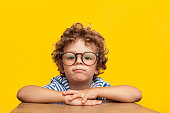 Little curly boy in glasses leaning on wooden box looking at camera on orange background.