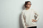 Portrait of charming woman hipster wearing blank sweater and eye glasses. Empty studio wall background