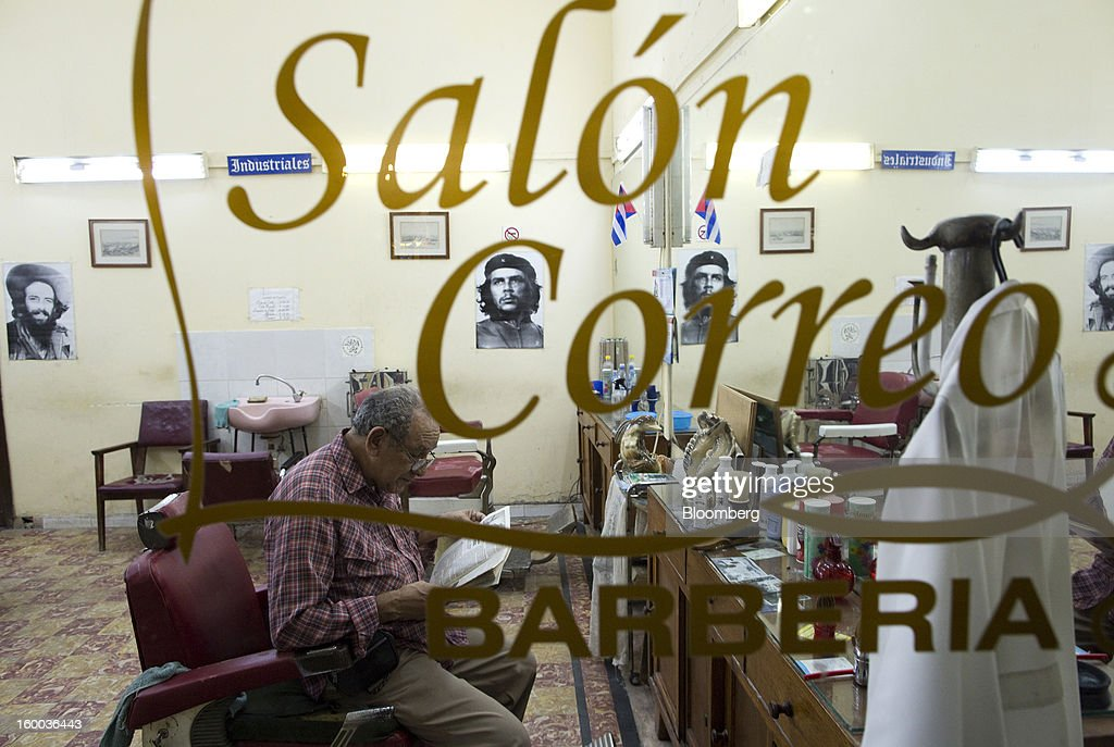 A portrait of Che Guevara hangs on a wall inside a barber's shop in Havana, Cuba, on Wednesday, Jan. 16, 2013. In a country where the average monthly salary is $19, according to Cuba's statistics agency, even buying an airplane ticket will be beyond the reach of most of the island's 11 million residents as President Raul Castro begins easing travel rules on the communist island. Photographer: Andrey Rudakov/Bloomberg via Getty Images