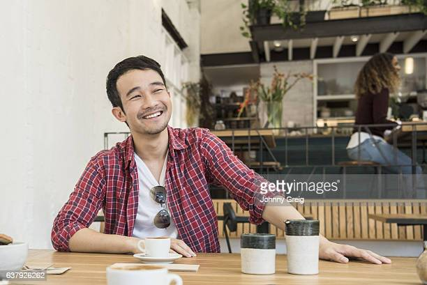 Portrait of cheerful Asian man in a cafe drinking coffee