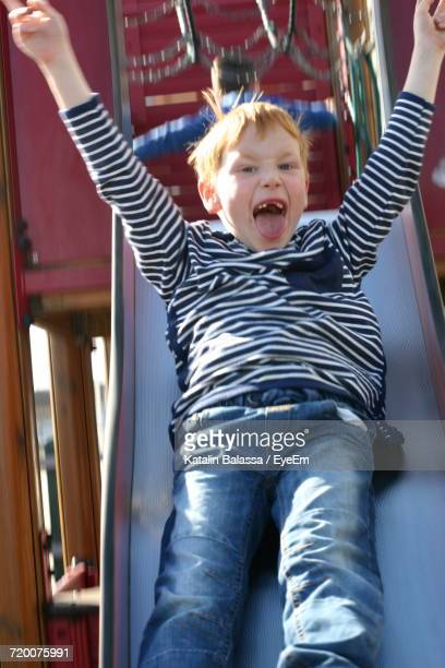 Portrait Of Cheerful Boy Sliding With Arms Raised At Playground
