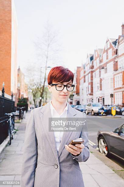 Portrait Of Cheerful Businesswoman Outdoors Texting On Smartphone