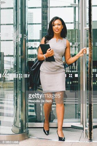 Portrait Of Cheerful Businesswoman Walking Through Revolving Doors