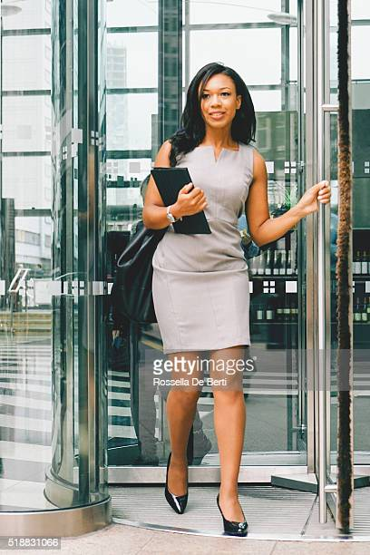 Portrait Of Cheerful Businesswoman Walking Through Revolving Doors