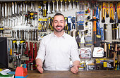 portrait of young cheerful european man at the cash desk working in tool-ware shop