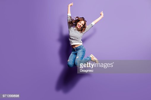 Portrait of cheerful positive girl jumping in the air with raised fists looking at camera isolated on violet background. Life people energy concept : Stock Photo