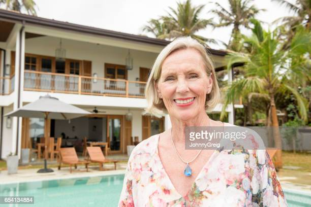 Portrait of cheerful senior woman on holiday wearing floral blouse