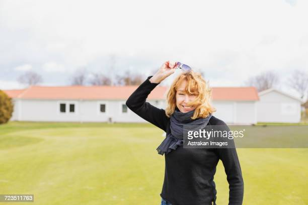 Portrait of cheerful woman removing sunglasses at golf course