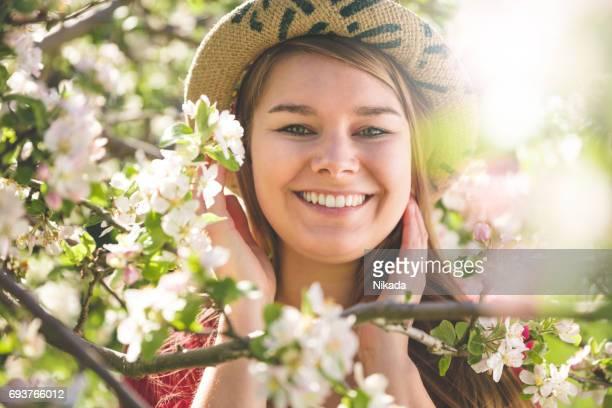 Porträt der stets gut gelaunte Frau mit Hut gesehen durch weiß blühende Apfelbaum