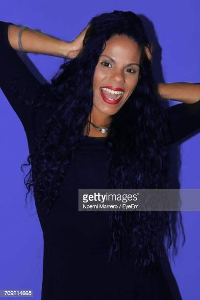 Portrait Of Cheerful Woman With Hand In Hair Against Blue Background