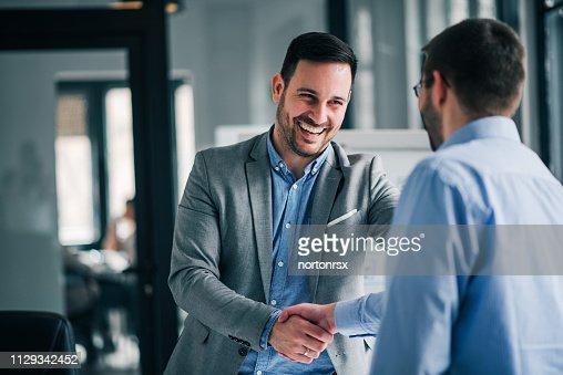 新入社員と陽気な若いマネージャーのハンドシェイクの肖像画。 : ストックフォト