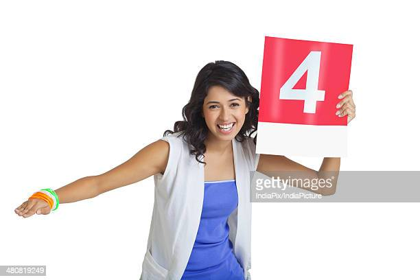 Portrait of cheerful young woman signaling four over white background