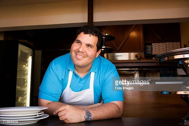 Portrait of chef behind restaurant counter.