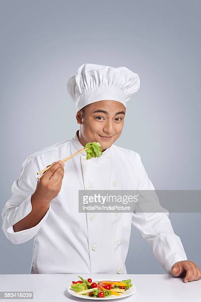 Portrait of chef holding lettuce with chopsticks