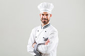 Portrait of chef smiling on gray background.