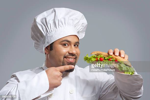 Portrait of chef pointing at sandwich