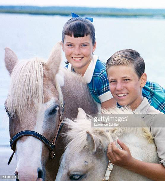 Portrait of child actors Pam Smith and David Ladd as they pose with a pair of ponies during the production of the film 'Misty' Chincoteague Island...