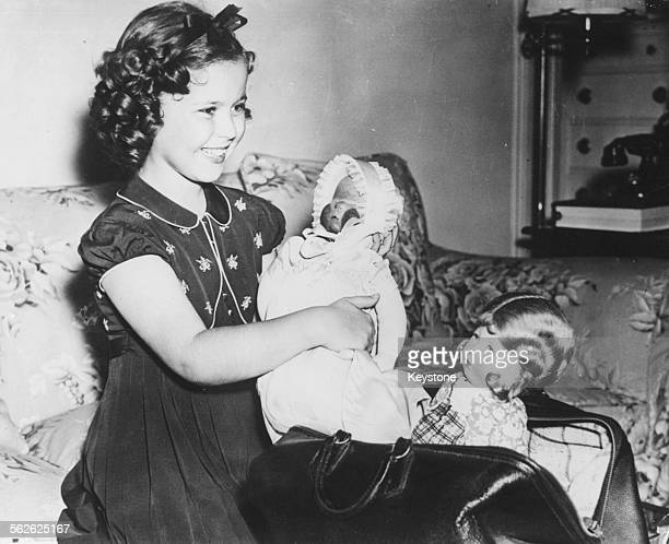 Portrait of child actress Shirley Temple holding her doll at the Waldorf Astoria in New York 1938