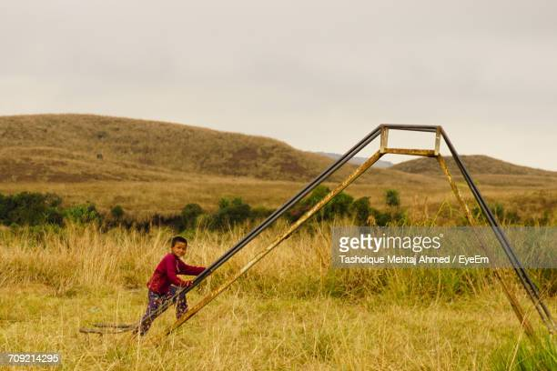 Portrait Of Child Climbing On Play Equipment At Grassy Field Against Clear Sky