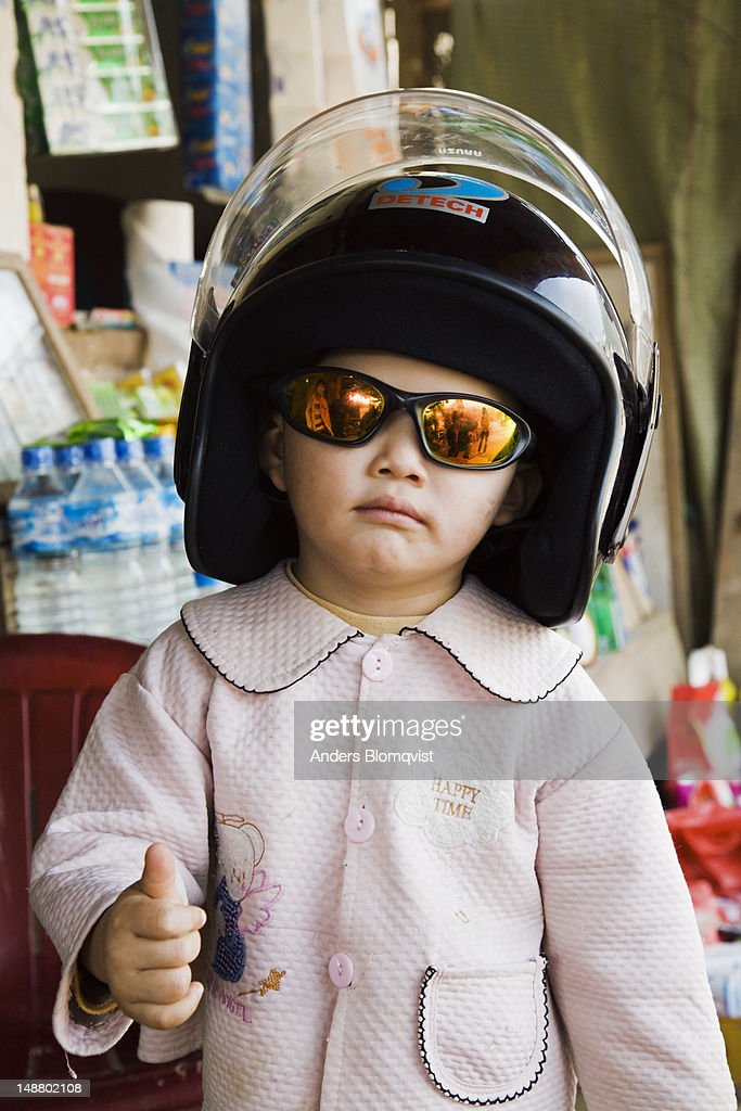 Portrait of child dressed in big helmet and hip sunglasses giving thumbs up. : Stock Photo