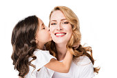 portrait of child kissing smiling mother isolated on white