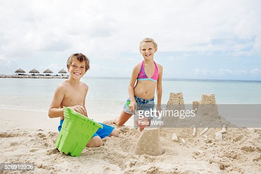 Portrait of children (10-12) playing on beach in sand : Stock-Foto