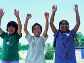 Portrait of children raising hands