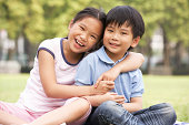 Portrait Of Chinese Boy And Girl Sitting In Park Together Smilng At Camera