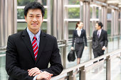 Portrait Of Chinese Businessman Outside Office With Colleagues In Background