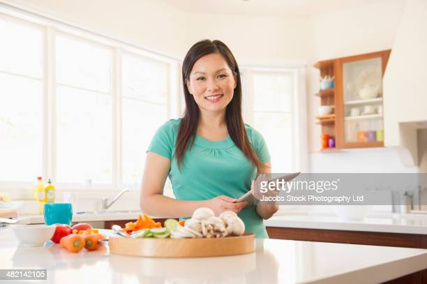 Portrait of Chinese woman with digital tablet in kitchen