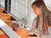 Portrait of Chinese young girl play with her cat at home in sunny afternoon, happy pets lifestyle.