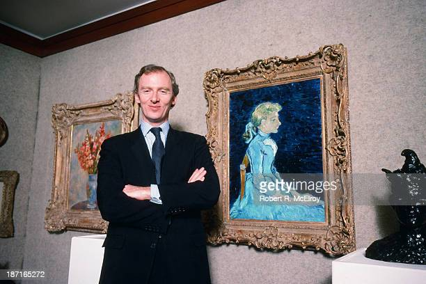 Portrait of Christie's auctioneer Christopher Burge standing in front of Van Gogh's 'Portrait of Adeline Ravoux' which is soon to be auctioned March...