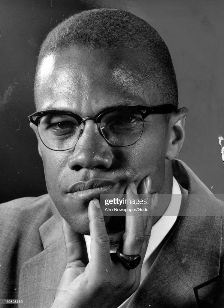 Portrait of civil rights leader Malcolm X with his hand on his chin looking inquisitive and wearing glasses circa 1965