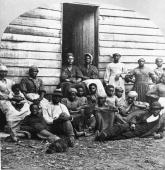 Portrait of Civil War 'contrabands' fugitive slaves who were emancipated upon reaching the North sitting outside a house possible in Freedman's...