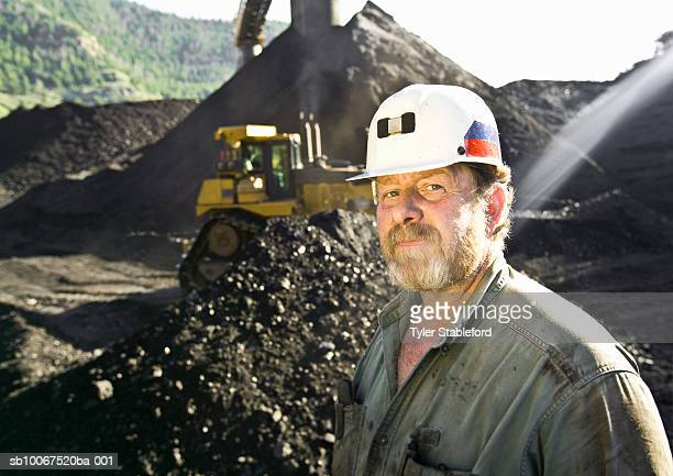 Portrait of coal miner standing in front of bulldozer on pile of coal