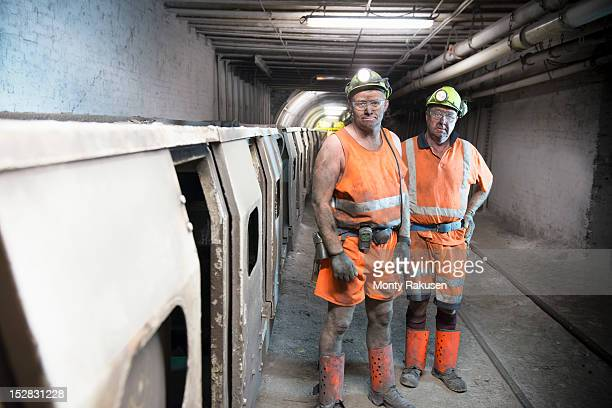 Portrait of coalminers working next to train in deep mine