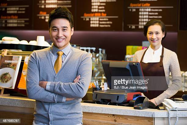 Portrait of coffee store shopkeeper and waitress