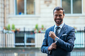Mature handsome man dressed in smart clothing in London, England. Man is expressing positive emotions and confidence