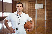 Portrait of confident basketball coach holding ball while standing in court